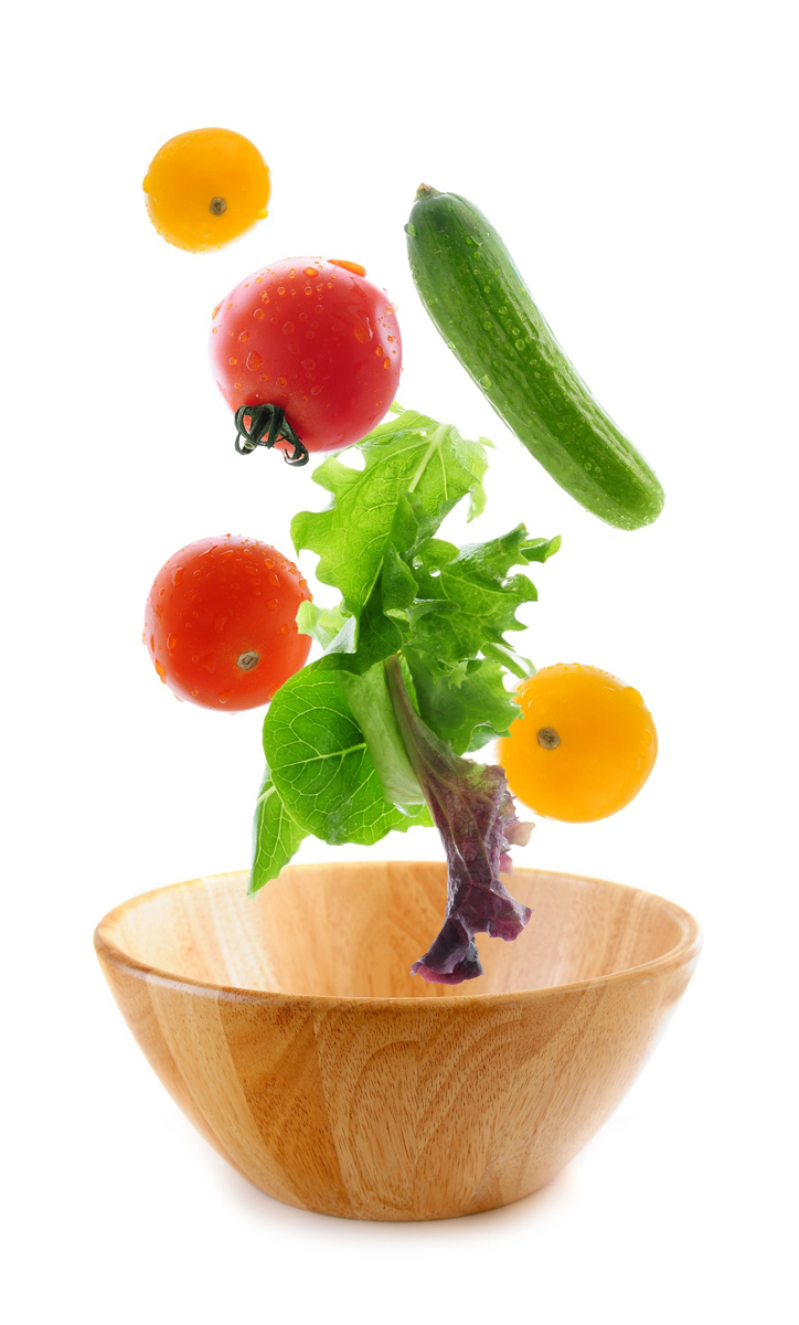 Assorted fresh vegetables falling into a wooden salad bowl isolated on white background
